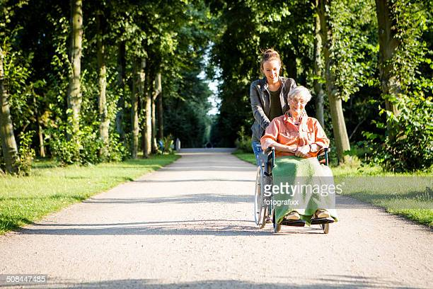 young woman pushing senior lady in wheelchair through a park