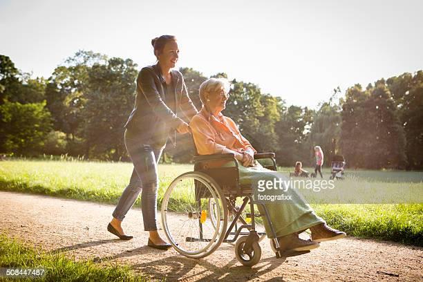 Jeune femme poussant senior femme en fauteuil roulant à travers un parc