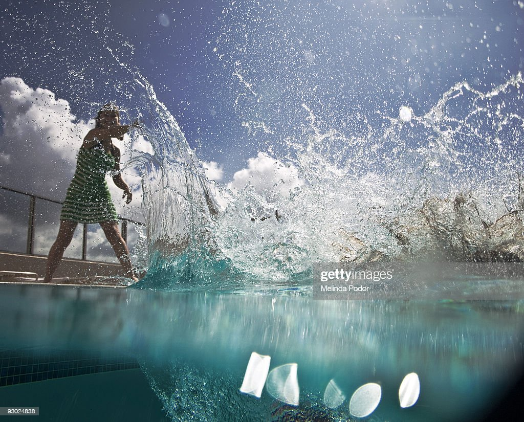 Young woman pushing someone in the water : Stock Photo
