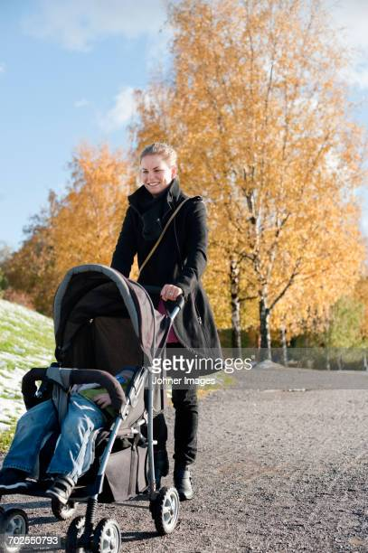 Young woman pushing stroller in park