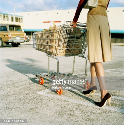 Young woman pushing trolley full of groceries in car park, low section : Stock Photo