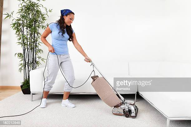 Young Woman Pushing Vacuum Cleaner