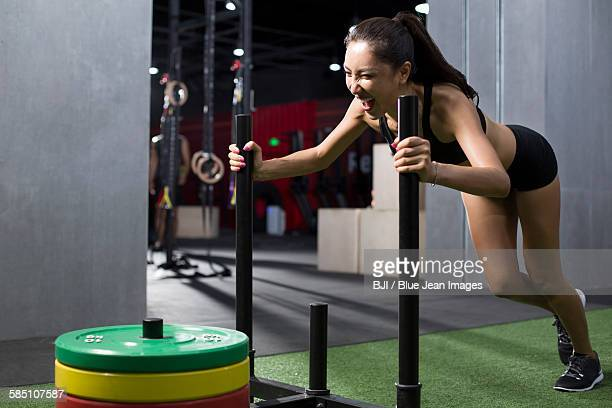 Young woman pushing weight sled at gym