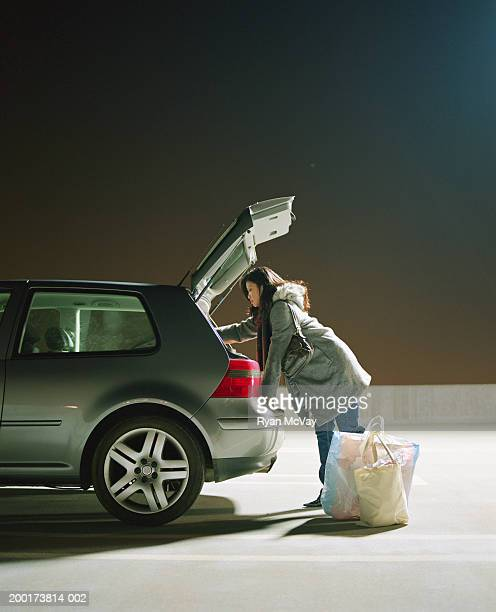 Young woman putting bags into trunk of car (low section)