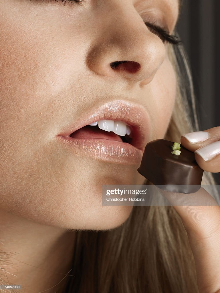 Young woman putting chocolate candy to mouth, portrait, close-up : Stock Photo