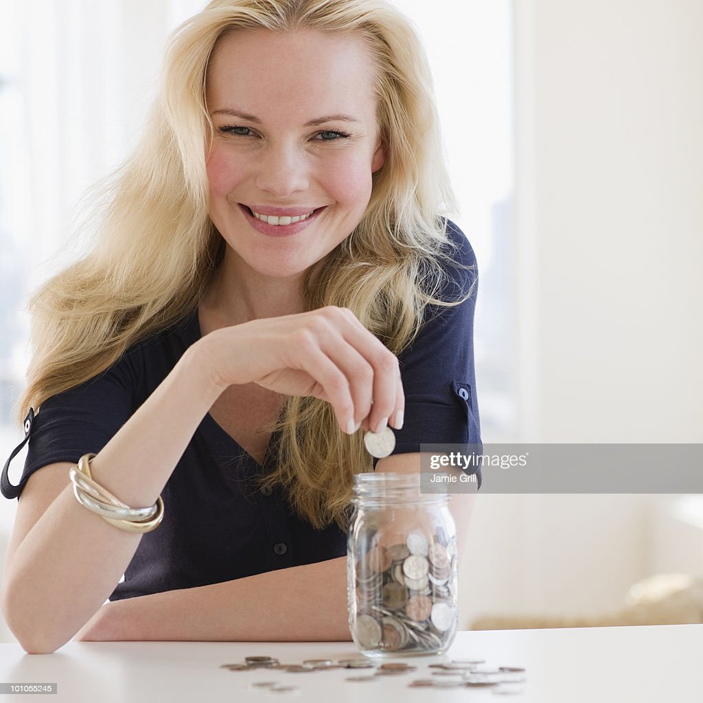 Young woman putting coin in jar of money : Stock Photo