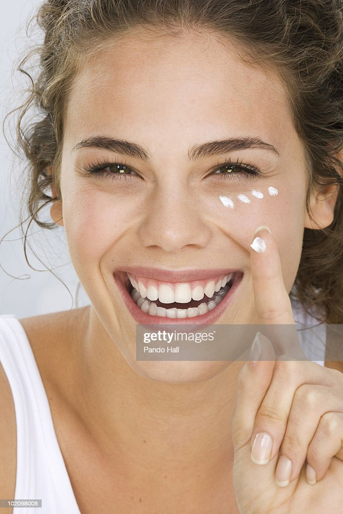 Young woman putting cream on face, smiling : Stock Photo