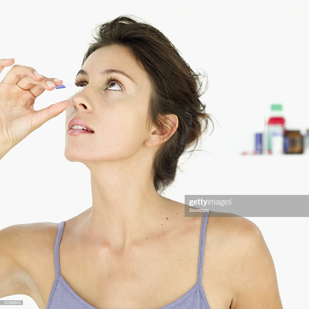 Young woman putting eye drops in her eye