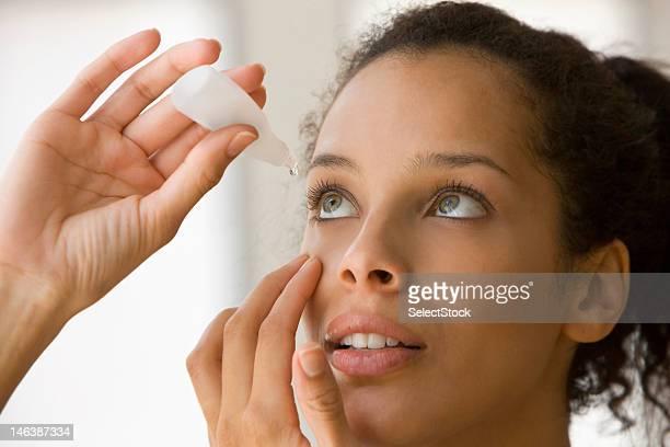 Young woman putting eye drops
