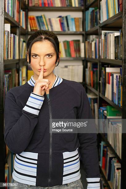 Young woman putting her fingers to her lips