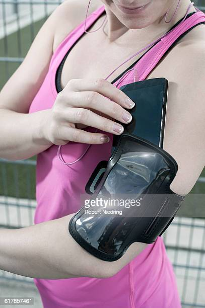 'Young woman putting mobile phone in her arm band, Bavaria, Germany'