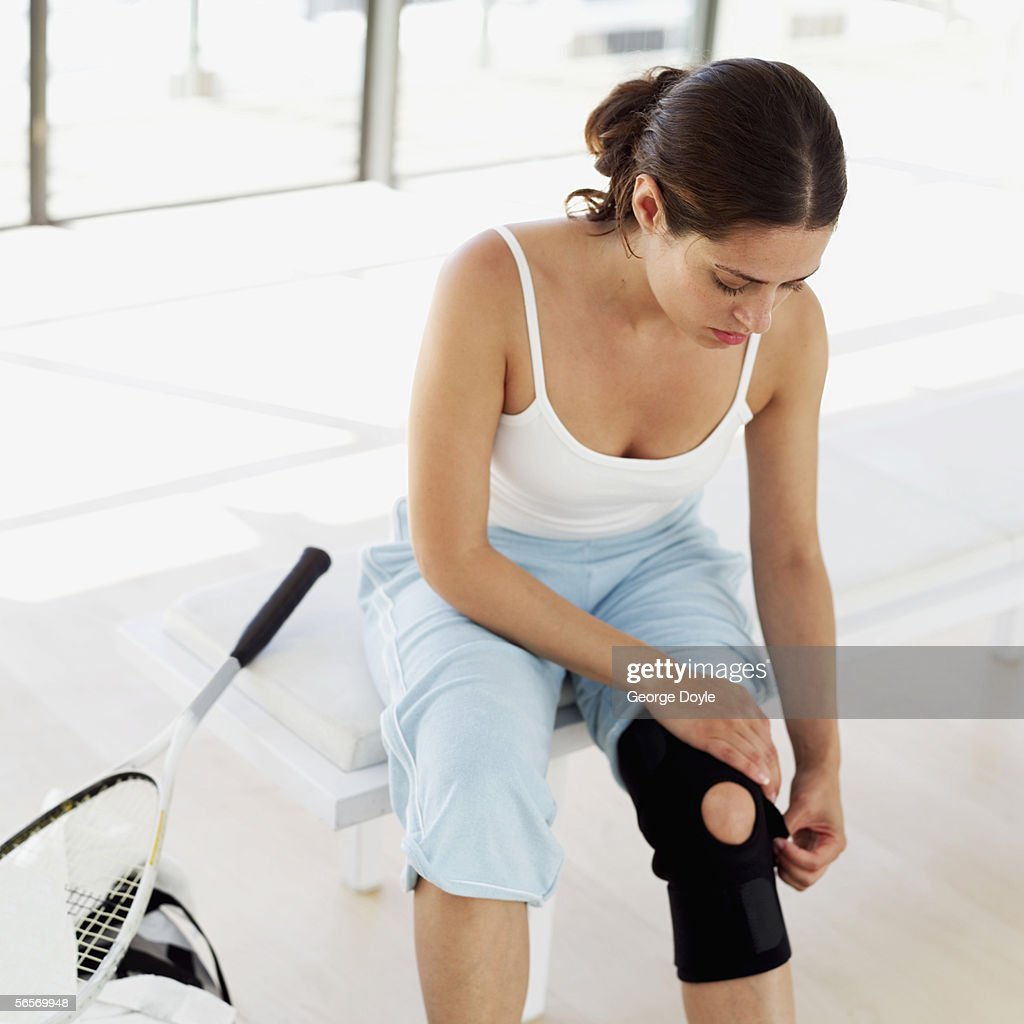 young woman putting on a knee pad