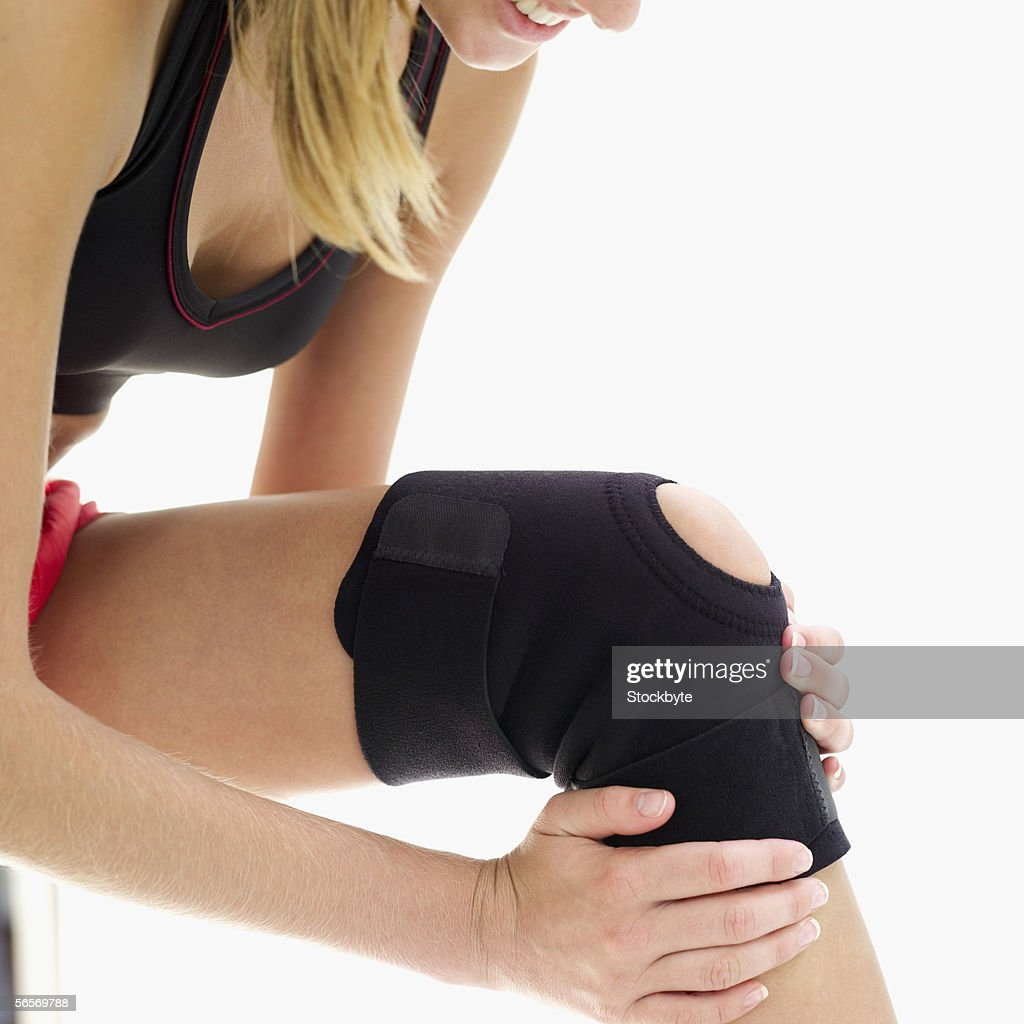 young woman putting on a kneepad