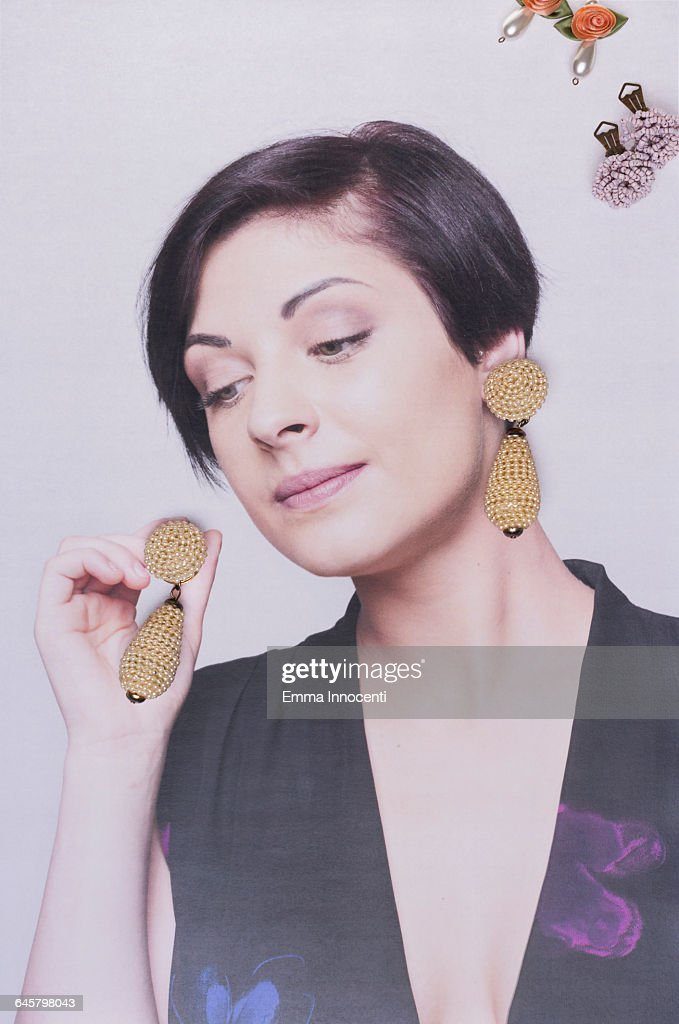 young woman putting on earings