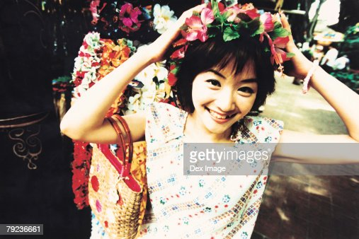 Young woman putting on garland on head : Stock Photo