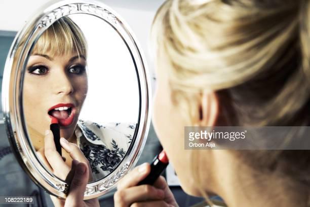 Jeune femme mettant le rouge à lèvres, regardant dans le miroir