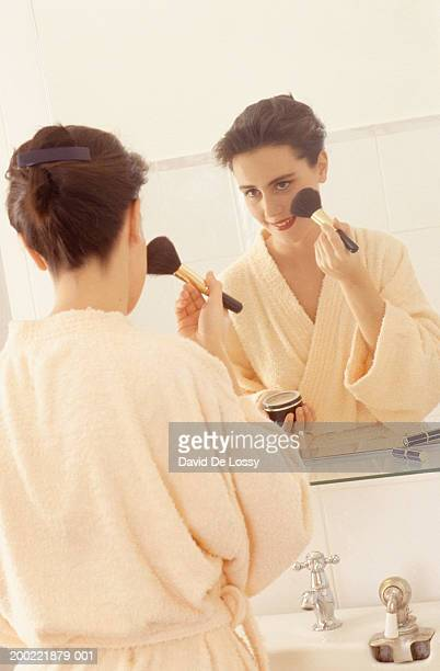 Young woman putting on make-up in front of bathroom mirror
