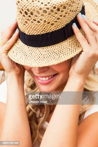 Young woman putting on straw hat : Stock Photo