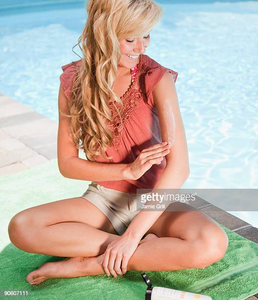 Young woman putting on suntan lotion by the pool