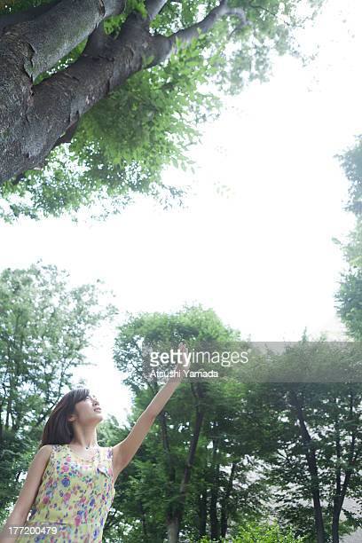 Young woman raising arm in forest