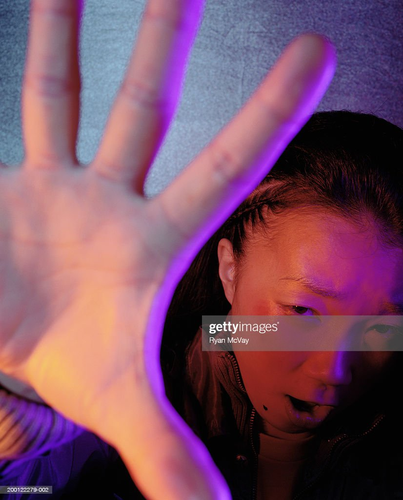 Young woman raising arm to shield herself, close-up : Stock Photo