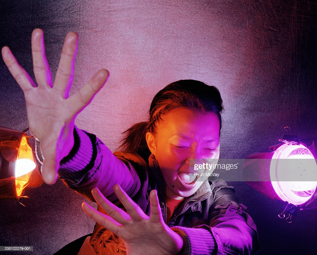 Young woman raising arms to shield herself, close-up : Stock Photo