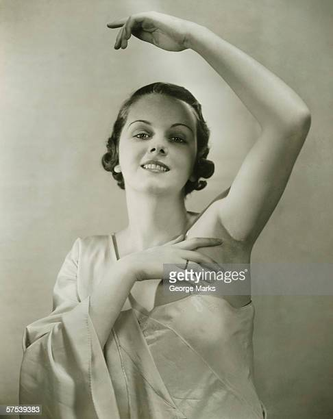 Young woman raising hand, posing in studio, (B&W), portrait
