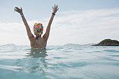 Young woman raising hands in ocean at dusk, St John, US Virgin Islands, USA