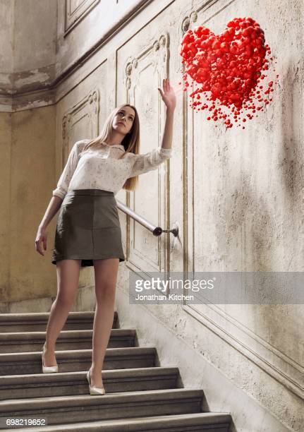 young woman reaches for a red heart . she is dressed stylishly and mesmerised by the heart and reaches for it