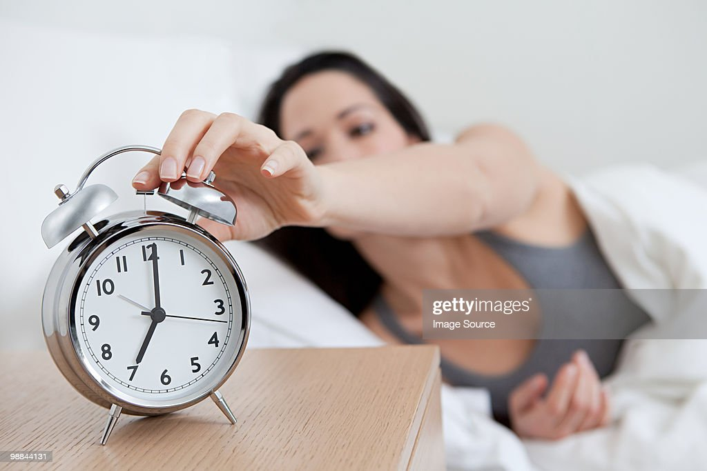 Young woman reaching for alarm clock : Stock Photo