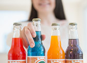 Young woman reaching for colorful bottles of soda