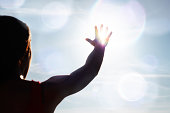 Young woman reaching for the sun, with flare.