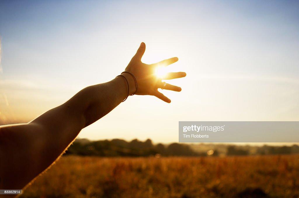 Young woman reaching hand towards sun  : Stock Photo