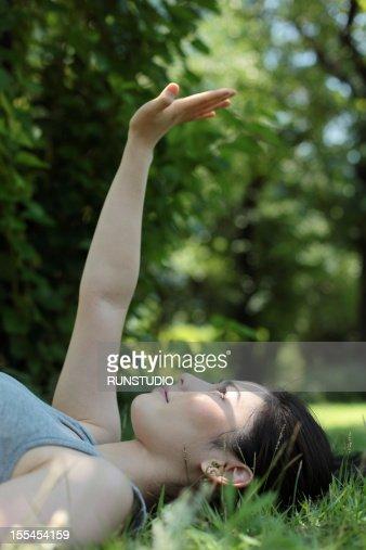 young woman reaching hand towards the sun : Stock-Foto