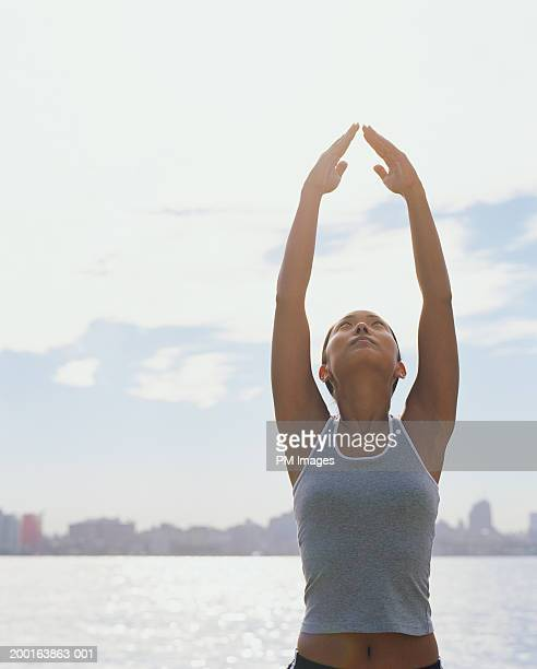 Young woman reaching hands up for yoga pose