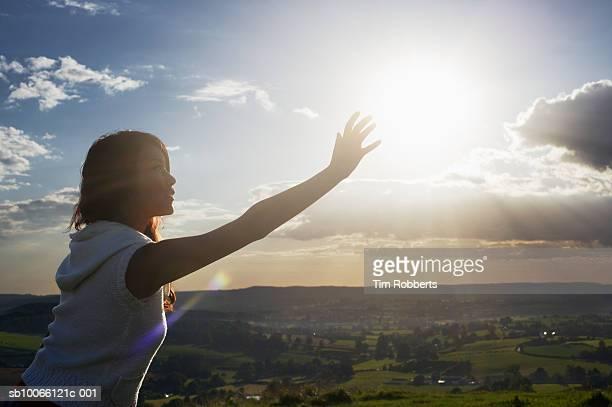 Young woman reaching her hand to sun, dusk