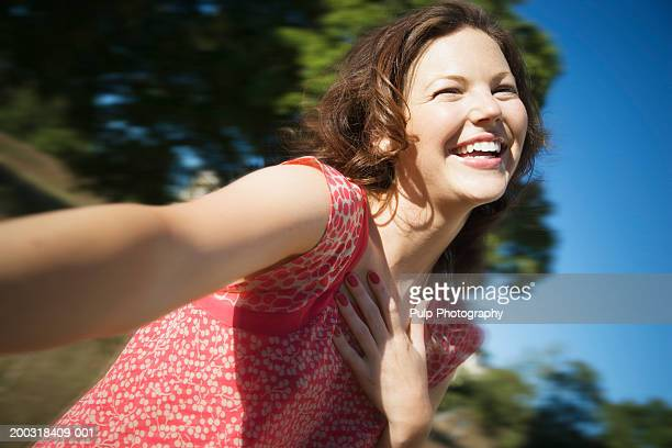 Young woman reaching out, hand on chest, laughing, close-up