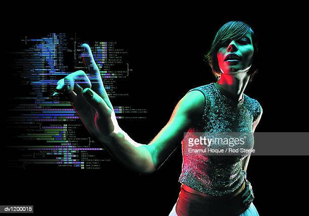 Young Woman Reaching Out to Push a Futuristic Touch Sensitive Computer Monitor Displaying Data