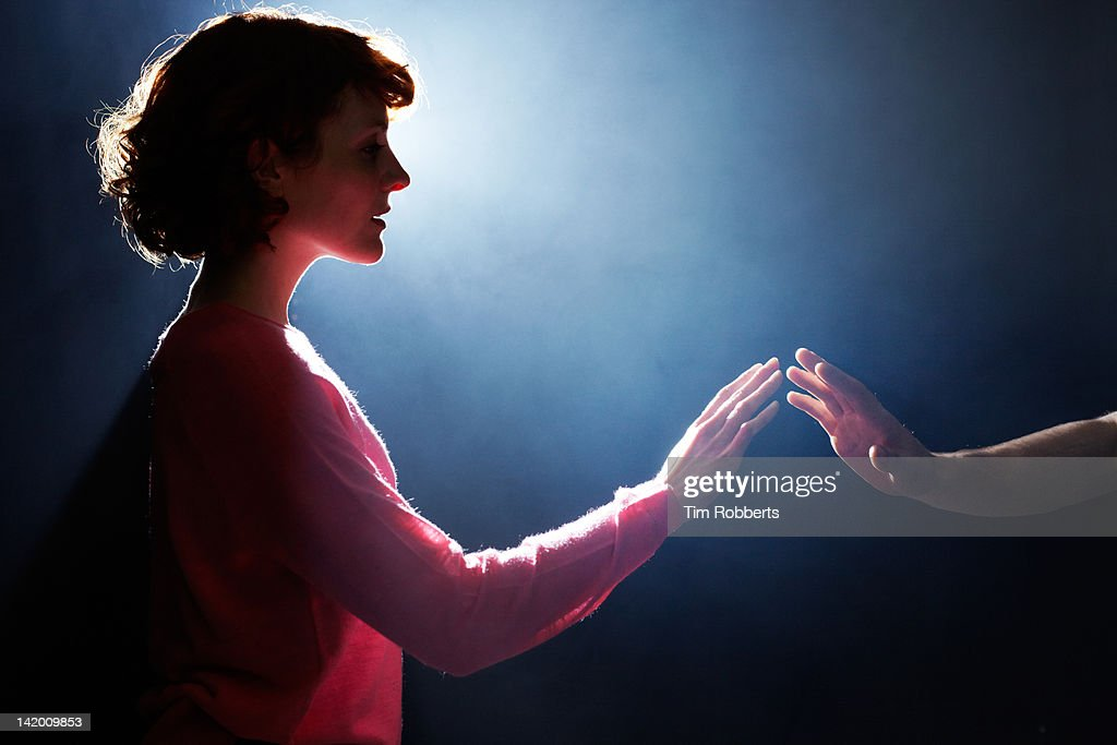Young woman reaching towards man.