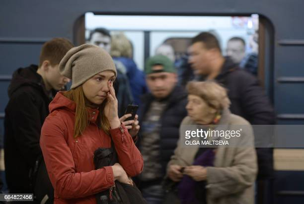 A young woman reacts by a makeshift memorial for the victims of April 3 metro blast at Technological Institute station in Saint Petersburg on April 5...