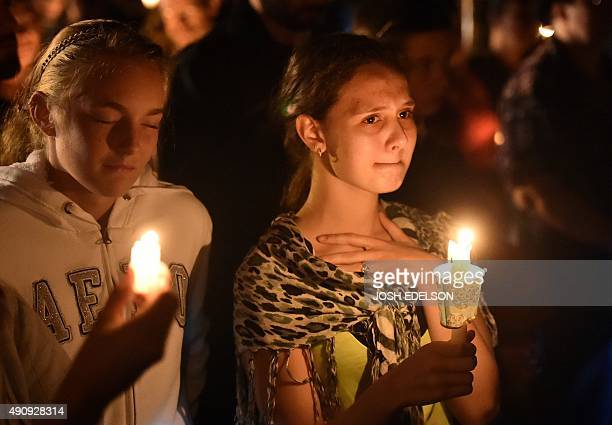 A young woman reacts during a vigil in Roseburg Oregon on October 1 for ten people killed and seven others wounded in a shooting at a community...