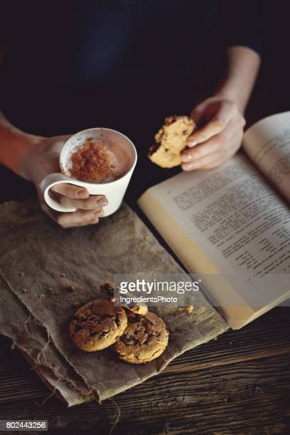 Young woman reading a book and drinking coffee with cookies on a wooden table.