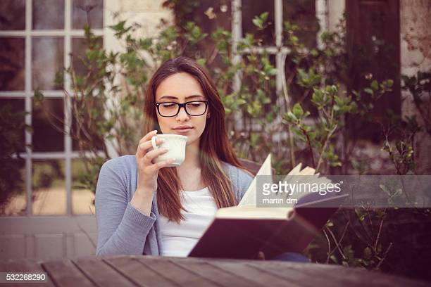Young woman reading a book at the veranda