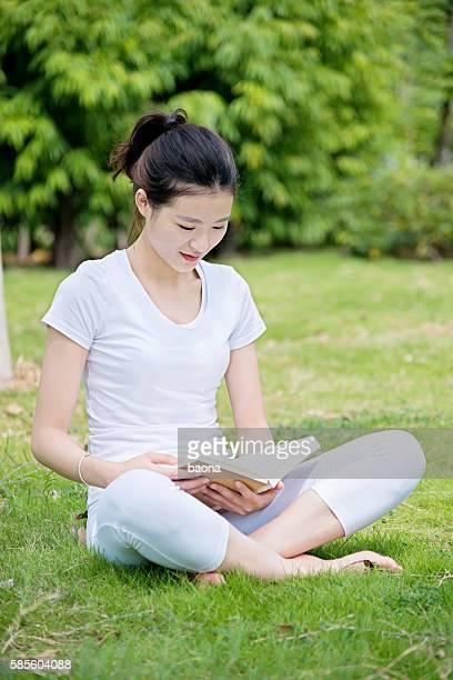 Junge Frau liest ein Buch im park