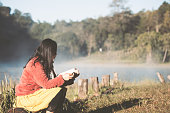 Young woman reading a book in the nature park with freshness in the morning with sunlight in vintage color tone