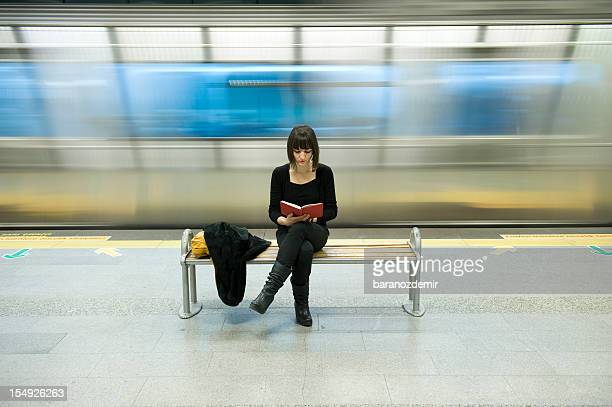 Young woman reading a book in the subway station