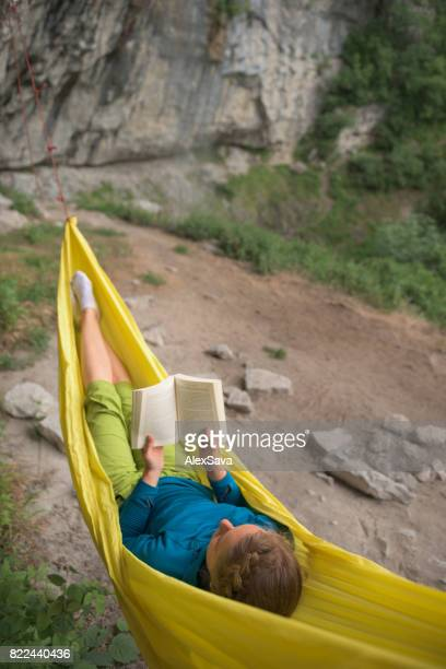 Young woman reading a book in yellow hammock outdoor in nature