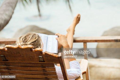 Junge Frau lesen ein Buch, während Sie sich auf einer tropischen Insel