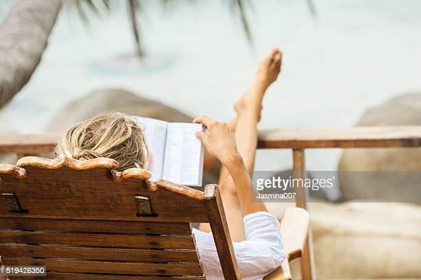 Mujer joven lee un libro mientras se relaja en una isla tropical