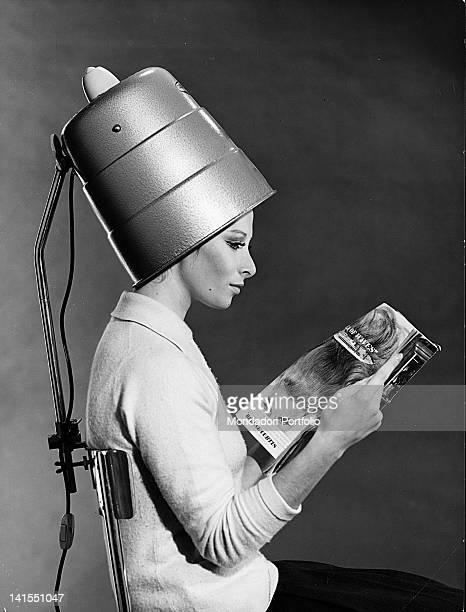 A young woman reading a magazine sitting on a chair with a back To this a support is attached which holds a hair drier for drying hair in the home...